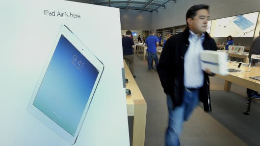 A customer walks out of the Apple store with his new Apple Inc. iPad Air in Palo Alto, California.
