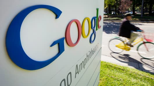 A bicyclist rides his bike past a Google Inc. sign at the company's headquarters in Mountain View, Calif.