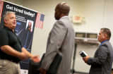 A job recruiter speaks with prospective employees as he recruits for his company during a job fair for veteran job seekers at the Harvey W. Seed American Legion Post 29 in Miami, Florida.
