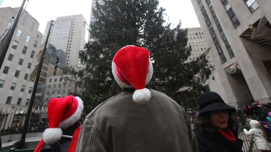 People wear Santa hats as they stand beneath the Christmas tree at Rockefeller Center.