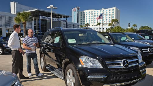A sales associate, left, assists a customer with a Mercedes-Benz GL sports utility vehicle at a car dealership in Fort Lauderdale, Fla.