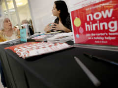 Jessica Cortes looks for part-time work at Carter's Children's Wear during a job fair in Sunrise, Fla.