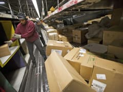 Workers handle packages at a UPS sorting facility in San Francisco.