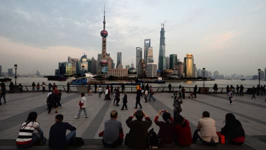Tourists view the Pudong financial district skyline from the historic Bund in Shanghai on October 29, 2013.