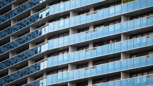 A woman looks out of a balcony at Marina Bay Residences in the central business district of Singapore.