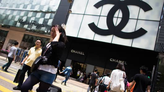 Pedestrians cross the street in front of a Chanel SA store in the Tsim Sha Tsui area of Hong Kong, C