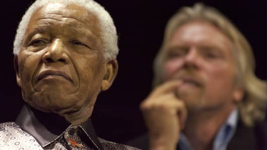 Former South African President Nelson Mandela, left, and U.K. billionaire Richard Branson listen to Peter Gabriel sing 'Biko,' in Johannesburg, South Africa.