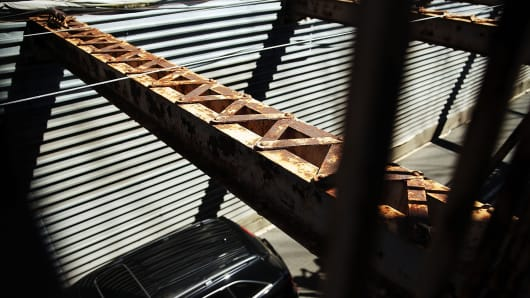 A car travels under rusty beams along the Brooklyn Bridge on September 18, 2013 in New York City.