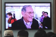 People watch a TV news program showing U.S. citizen Merrill Newman released by North Korea, at Seoul Railway Station in Seoul, South Korea, Saturday, Dec 7, 2013.