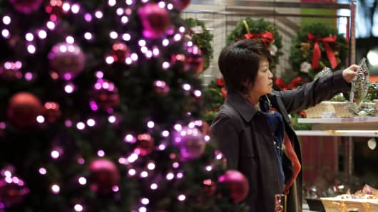 A woman looks at a Christmas decoration displayed for sale in Tokyo, Japan, on Thursday, Dec. 5, 2013.