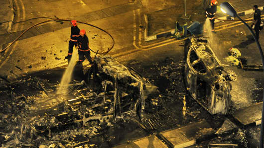 Firemen douse a charred ambulance and a car after a riot broke out in Singapore, in the early hours of December 9, 2013.