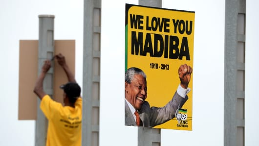 ANC members put up posters at FNB Stadium in preparation for Nelson Mandela's memorial service, Dec 9, 2013.
