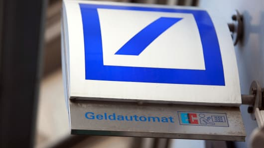 A Deutsche Bank AG logo sits on a sign for an automated teller machine (ATM) in Berlin, Germany.