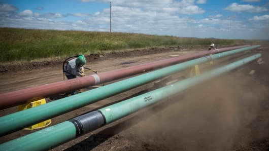 A construction worker specializing in pipe-laying sandblasts a section of pipeline in North Dakota.