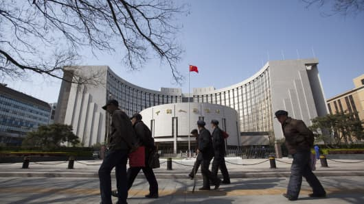 Pedestrians walk past the People's Bank of China in Beijing, China