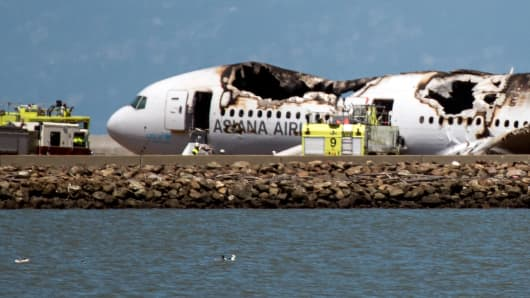 A burned Boeing Co. 777, operated by Asiana Airlines Inc., sits on the runway after it crashed landed at San Francisco International Airport (SFO) in San Francisco, California on July 6, 2013.