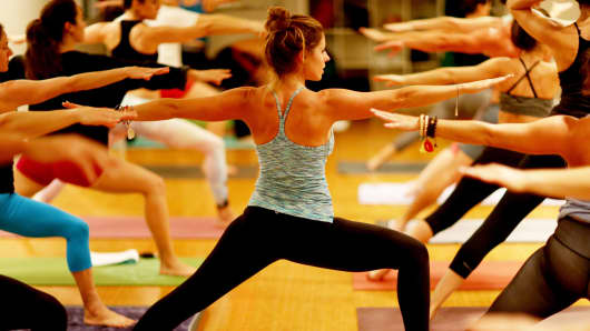 A woman wearing Lululemon Athletica clothing leads a yoga class in Miami Beach, Florida