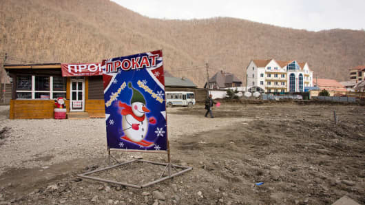 "A sign that reads ""Tickets"" with a skiing snowman stands in the middle of a snow-free skiing area last February, near Sochi 2014 Olympic venues."