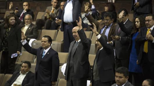 Deputies vote during a session to debate oil industry reforms at the Mexican Congress in Mexico City, Mexico, on Thursday, Dec. 12, 2013.