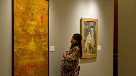 A visitor looks at a painting during a media preview ahead of Christie's first auction in India, in New Delhi on December 6, 2013.