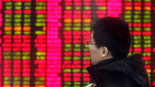 Man looks at share prices at an electronic stock board in Shanghai, China.