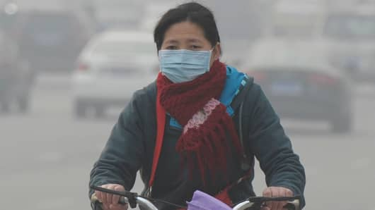 A cyclist wearing mask rides along a road on December 5, 2013 in Nanjing, China.