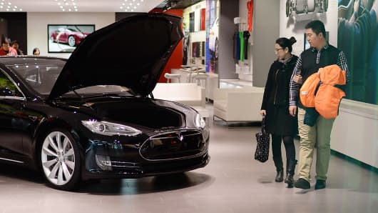 A couple view a Tesla Model S sedan displayed in a Beijing showroom.
