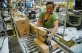 An Amazon.com employee loads boxes onto a conveyer belt for shipping at the company's distribution center in Phoenix.