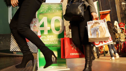 People carry shopping bags along Broadway on December 2, 2013 in New York City.