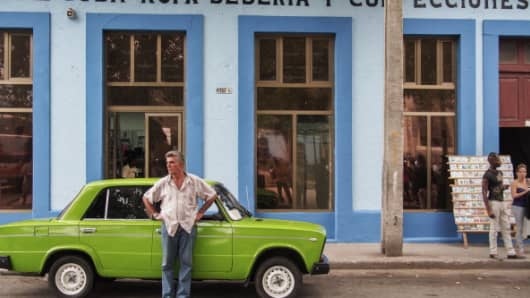 A driver stands by his green Lada in Matanzas, Cuba