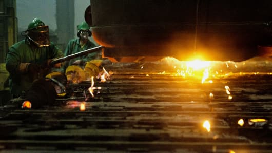 Molten steel is poured into molds for railraod car suspension parts at the Columbus Castings foundry in Columbus, Ohio.