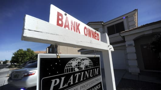 In this file photo, A bank owned sign hangs outside a home for sale in Las Vegas.