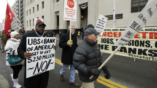 The Rev. Charles Williams II, left, leads Detroit city workers in a protest outside the federal courthouse in Detroit while awaiting the bankruptcy decision, Tuesday, Dec. 3, 2013.