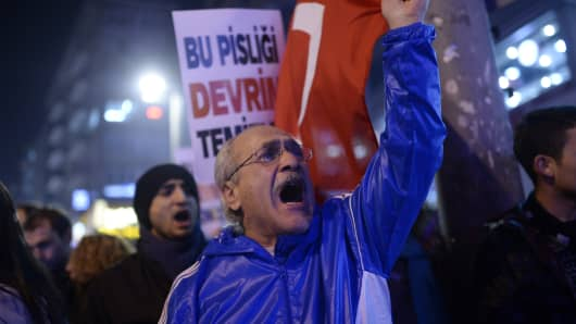 A protestor chants slogans and waves a Turkish flag during a demonstration against corruption in the Kadikoy district of Istanbul on December 25, 2013.