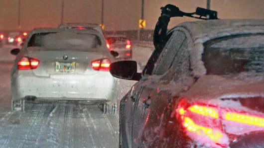 A driver reaches out to clear their windshield of snow and ice while navigating the Leverett Connector, Boston.
