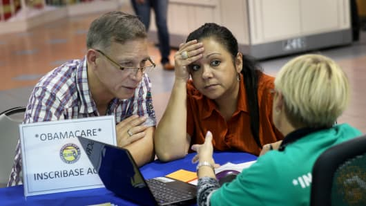 A couple speaks with an insurance agent as they try to purchase health insurance under the Affordable Care Act in Miami, Florida.