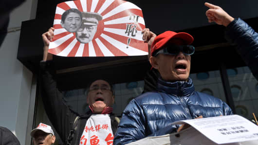 Demonstrators shout slogans as a man holds up a banner with the faces of current Japanese Prime Minister Shinzo Abe and Japanese World War II prime minister Hideki Tojo during an anti-Japan protest in Hong Kong on December 27, 2013.