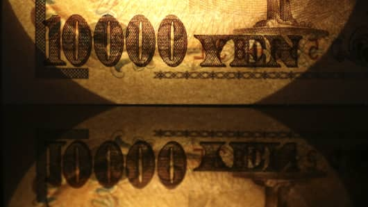 A Japanese 10,000 yen banknote is reflected in a table.