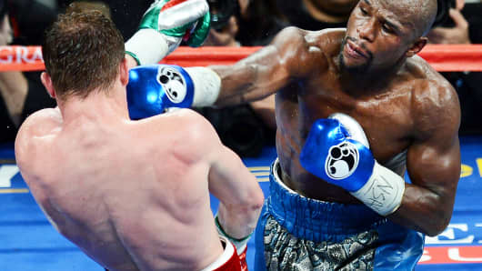 Floyd Mayweather Jr. (R) hits Canelo Alvarez in their WBC/WBA 154-pound title fight at the MGM Grand Garden Arena on Sept. 14, 2013, in Las Vegas.
