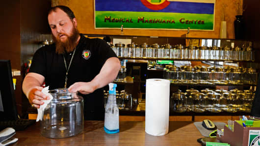 A man cleans jars that will hold recreational marijuana at 3D Cannabis Center in Denver on Monday.