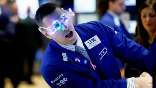 A trader wears glasses celebrating the new year while working on the floor at the New York Stock Exchange on Tuesday.