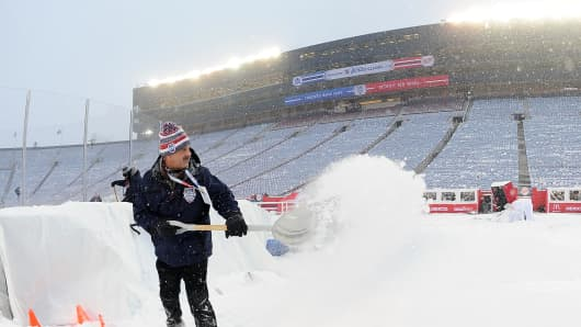 An ice crew member shovels snow Wednesday during the 2014 Bridgestone NHL Winter Classic at Michigan Stadium in Ann Arbor, Jan 1, 2014.