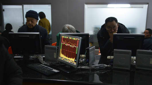 Photo taken on December 30, 2013 shows investors looking at stock prices on screens in a securities exchange in Shanghai.