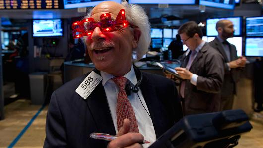 A trader wears 2014 novelty glasses on the floor of the New York Stock Exchange.