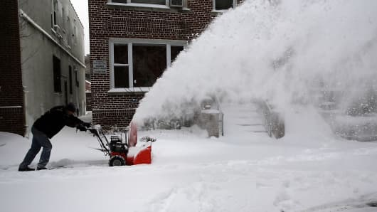 A man clears a sidewalk in Brooklyn on Friday after a storm that left up to 8 inches of snow in New York.