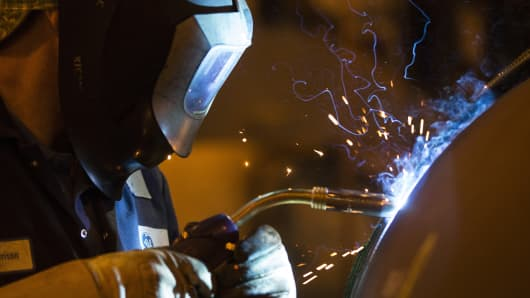 A worker welds a gas and oil rig connector pipe at the General Electric maintenance plant in Montrose, U.K.