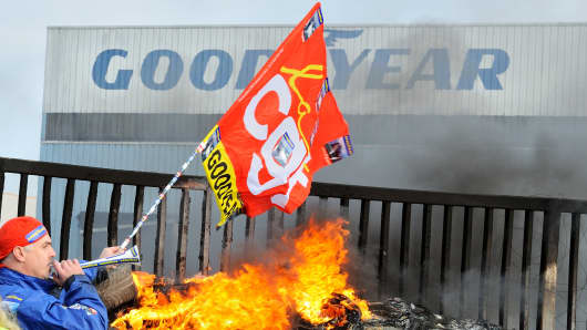 An employee waves a flag and blows a horn next to burning tyres in front the US Goodyear tyremaker site in Amiens, northern France, on December 5, 2013 after the announcement of the shutdown of the factory.