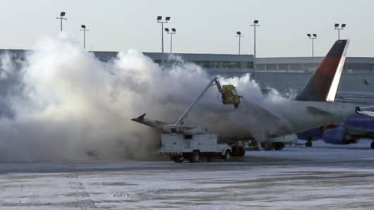 A Delta plane is deiced at Chicago Midway International Airport on Monday.