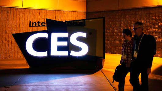 Attendees walk past signage outside the Las Vegas Convention Center during the 2014 Consumer Electronics Show in Las Vegas, Monday, Jan. 6, 2014