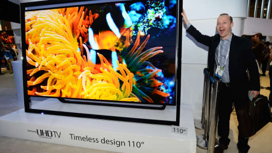 An attendee poses next to Samsung's 110-inch 4K television at the 2014 International CES in Las Vegas.